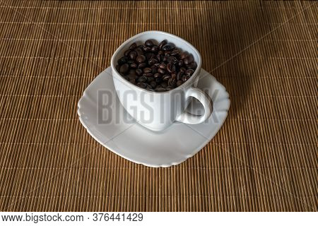 Roasted Coffee Grains In A White Cup Standing On A Saucer Close Up