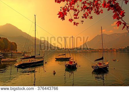Beautiful Autumn Scene In Italy, Lake Como. A Lot Of Boats, Red Leaves And Mountains On The Backgrou