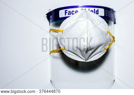 A Face Mask Covered On A Face Shield Placed On A White Surface. To Use For Personal Protection Again