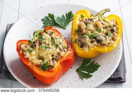 Stuffed Sweet Peppers With Rice Mushrooms And Cheese With Herbs. Baked Halves Of Red And Yellow Pepp