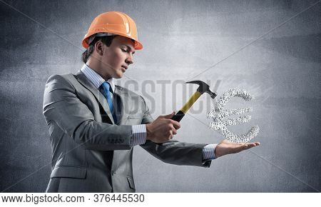 Businessman Going To Crash With Hammer Euro Currency Sign. Young Handsome Man In Business Suit And S