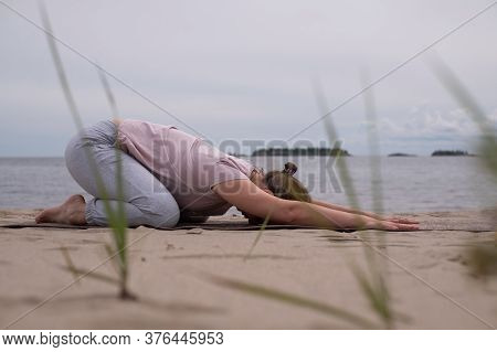 Sporty Young Woman Practicing Yoga, Sitting In Child Exercise, Balasana Pose