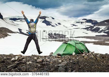 Hiker Man With Backpack And Tent Jumping With Outstretched Arms. Camping In Snow Mountain Glaciers A