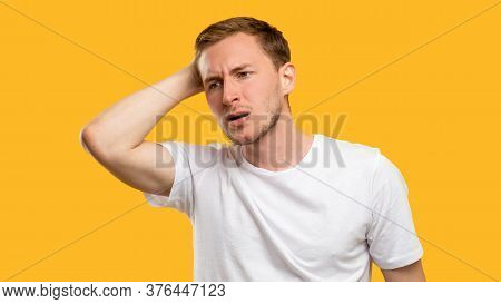 Troubled Man Portrait. Mistake Regret. Concerned Guy Touching Head Isolated On Orange Background.