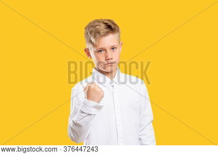 Angry Boy Portrait. Threat Power. Confident Aggressive Kid Warning With Fist Gesture Isolated On Yel