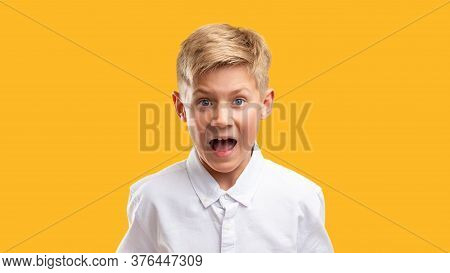 Scared Child Portrait. Panic Attack. Frustrated Boy In White Shirt Screaming Isolated On Orange Back