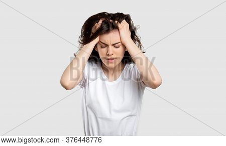 Frustrated Woman Portrait. Mental Disorder. Lady With Strong Headache Isolated On Light Background.