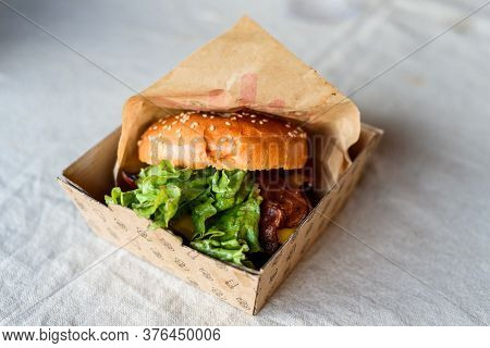 Burger With Bacon, Cheese And Lettuce On Table