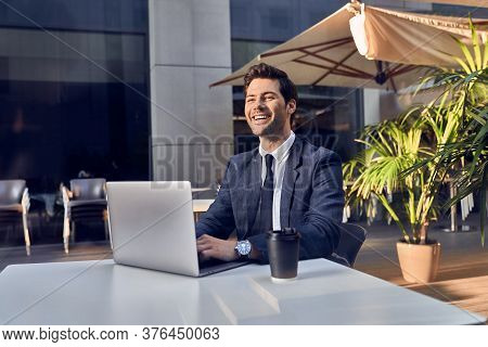 Young Successful Businessman Working On A Laptop While Sitting In Cafe During Work Break Lunch,thoug