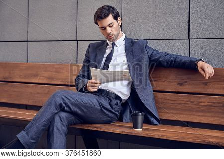 Daily News. Full Length Of A Pleasant Smiling Businessman Reading A Newspaper With Coffee While Sitt
