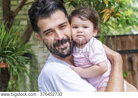 Cheerful Father Holding And Hugging His Baby Daughter In The Garden While Relax Time At Home. Mixed