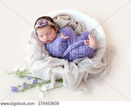 Charming newborn sleeping in round cradle with flowers
