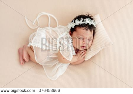 Cute newborn in lace dress sleeping on side with tiny pillow