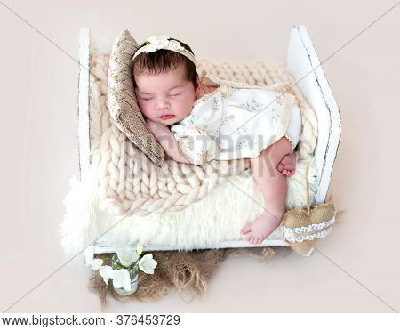 Funny newborn girl sleeping on tiny wooden bed