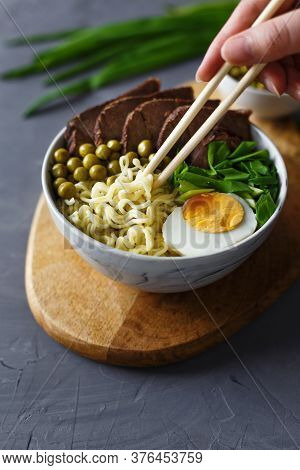 Vietnamese Pho Bo Soup In Bowl. Beef Pho Bo With Eggs And Green Peas. Noodles Picked Up With Chopsti