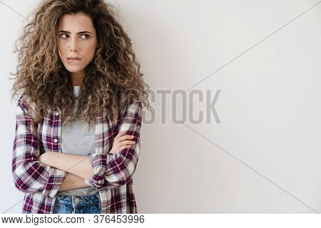 Photo of puzzled beautiful woman looking aside while posing on camera isolated over white background