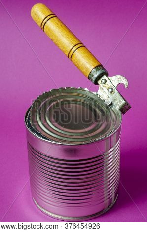 Canned Food On A Purple Background. An Old Can Opener With A Wooden Handle Opens A Can. Close-up. Co