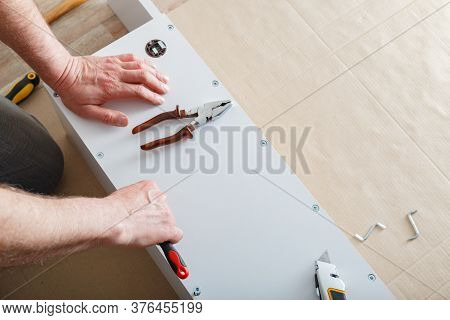 Furniture Assembly. Male Hands Master Collects Furniture Using Screwdriver Tools, Instrument At Home