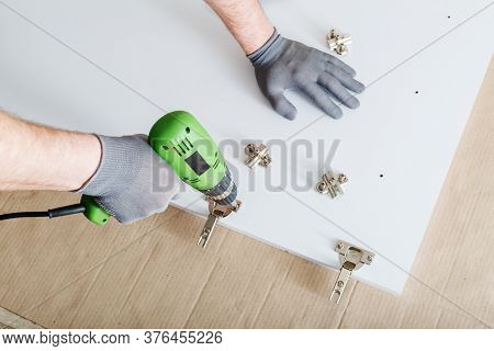 Furniture Assembly Using Drill. Male Hands In Gray Gloves, Master Collects Furniture Using Tools Ins