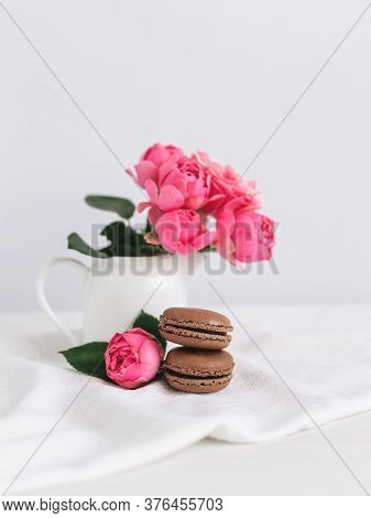Two Tasty French Macarons And A Jar With Beautiful Pink Roses On A White Background. Chocolate Macar