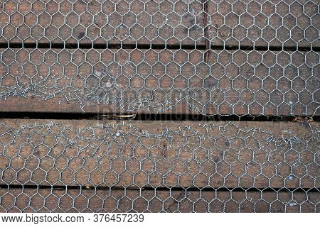 Repaired Wooden Plank Boardwalk Covered In Metal Wire Hexagonal Mesh With Staples Holding Down The D