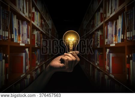 Hand Holding A Light Bulb With Bookshelf In Library Background. Concept The Idea Of Reading Books, K
