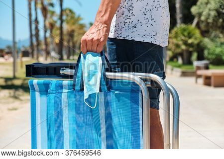 closeup of a caucasian man, wearing shorts, stading in the seafront, carrying a surgical mask and a folded beach chair in his way from or to the beach