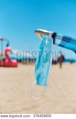 closeup of a surgical mask hanging on a blue deck chair on the beach, with the sea in the background