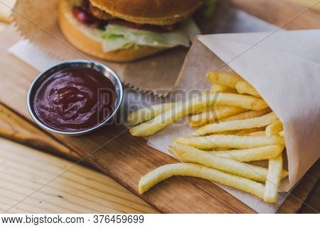Fresh Tasty Burger And French Fries On Wooden Table. French Fries And Bbq Sauce On Wood Plate. Stree