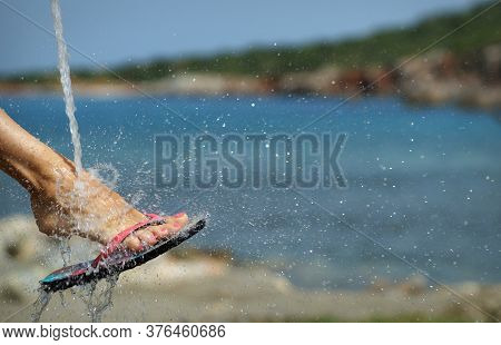 Closeup Of Single Foot In Summer Beach Slides Under Water Spray, Many Water Drops Splashing Around.