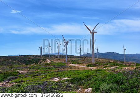 Windmill Turbine Farm On A Hilltop In Colorful Landscape With Winding Road Against Blue Sky On Clear