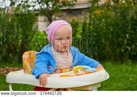 Baby In The Yard In A Walker, Little Boy Sitting In A Walker In The Garden