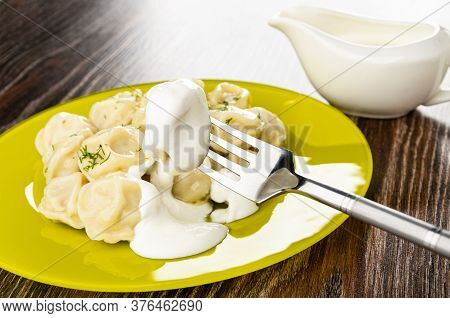 Yellow Glass Plate With Meat Dumplings Poured Sour Cream, Dumpling Strung On Fork, Sauce Boat With S