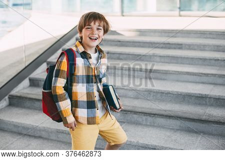 Happy Boy With A Backpack And A Book Goes To School. Beginning Of The New School Year After The Summ