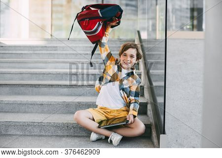 A Happy Boy In Glasses With A Backpack And A Tablet Sits On The Steps At The Entrance To The School.