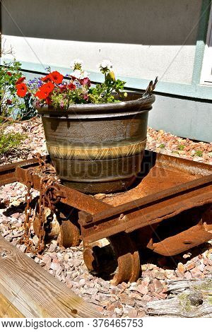 A Huge Flower Pot Full Of Beautiful Blooming Flower Rests On A Rusty Old Cart Used By Miners To Haul