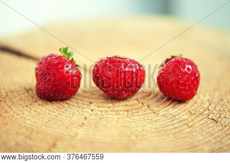Three Red Strawberries In A Row On The Wooden Background