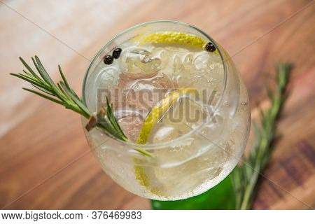 Closeup Glass Alcoholic Drink (gin And Tonic Cocktail) With Lemon, Rosemary And Ice On Rustic Black