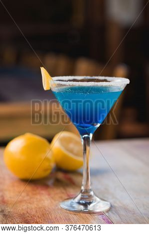 Blue Margarita Cocktail Drink, In Front, With Lemon In The Background, On Rustic Table