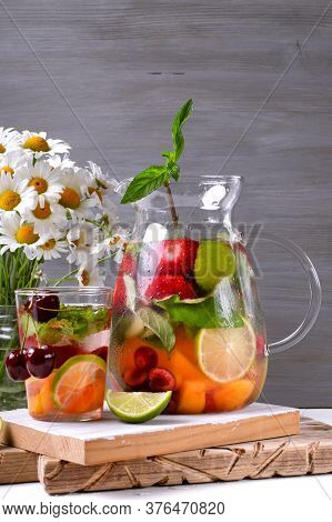 Infused Water With Fruits, Berries And Mint In Glass Pitcher Against The Grey Background