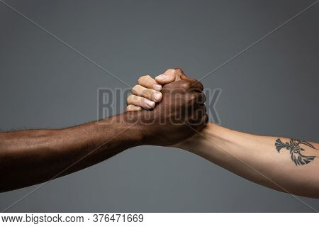 Teamwork. Racial Tolerance. Respect Social Unity. African And Caucasian Hands Gesturing On Gray Stud