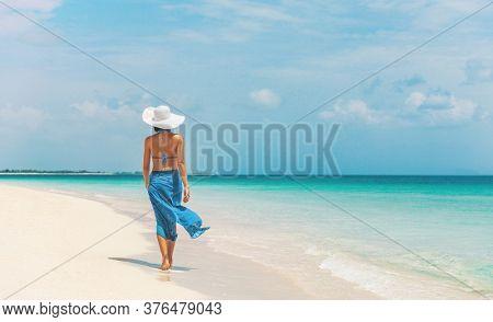 Caribbean beach vacation luxury elegant lady walking in blue beach wrap sarong skirt relaxing on idyllic holiday white sand beach stroll.