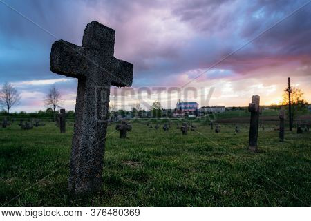 Old Tombstone In Old Abandoned Cemetery In Belarus Against Church And Sunset Sky