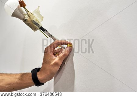 Close Up Of A Hand Holds A Dowel Near The Wall Process Of Installation Of A New Lamp In The House