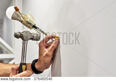 Close Up Of Worker Clogs A Dowel Into A Wall Using A Hammer To Install A New Lamp In The House