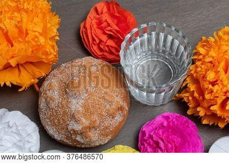 Detail Of An Altar For Day Of The Dead In Mexico. Bread, Flowers And Mezcal On A Table