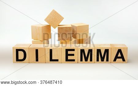 Dilemma - Word Written On Wooden Cubes On A White Background