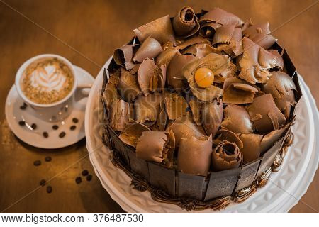 Chocolate Cake With Dark Chocolate Shavings On Top, In White Plate, Cup With Coffee In The Backgroun