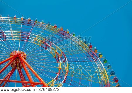 A Big Colourful Ferris Wheel Isolated On Blue Sky Background In Amusement Park