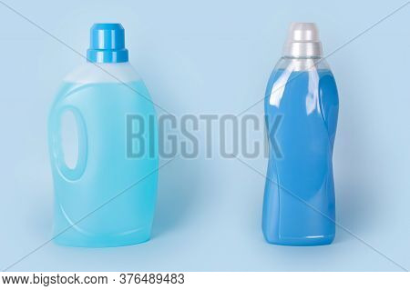 Bottles Of Detergent And Fabric Softener On Blue Background. Containers Of Cleaning Products, Househ